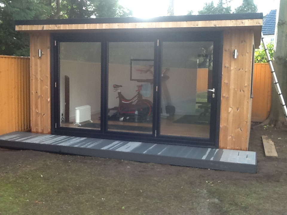 Gym with fully insulated walls, floor and ceiling, by fold doors and small composite decking walkway and a one-piece rubber roof.